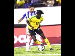Shamar Nicholson dribbles ahead of Honduran player Emilio Izaguirre  in their Concacaf Gold Cup match at the National Stadium last year.