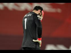 Liverpool's goalkeeper Alisson reacts after Manchester City's Raheem Sterling scored his side's third goal during the English Premier League match between Liverpool and Manchester City at Anfield Stadium, Liverpool, England, yesterday.
