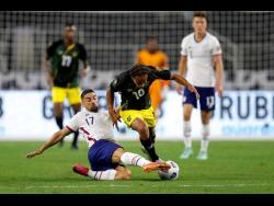 United States midfielder Sebastian Lletget (17) tackles Jamaica's Bobby Reid during their Concacaf Gold Cup quarter-final match in Arlington, Texas on Sunday, July 25. Both players are likely to clash again when both teams meet in a Concacaf World Cup qualifier in Austin, Texas, today