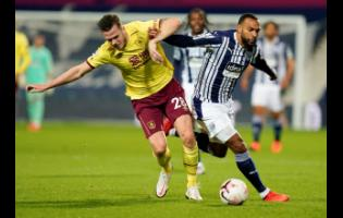 Burnley's Kevin Long ( left) and West Brom Albion's Matt Phillips battle for the ball during their English Premier League soccer match at The Hawthorns in West Bromwich, England, yesterday.