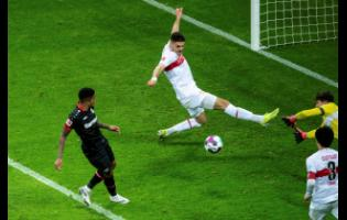 Leverkusen's Leon Bailey (left) scores against Stuttgart's Konstantinos Mavropanos and goalkeeper Gregor Kobel to make it 3-1 during their German Bundesliga match at BayArena in Leverkusen, Germany, on Saturday February 6.