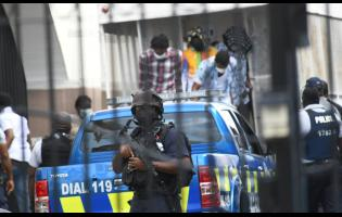 Police escort alleged members of the Clansman gang into court on the first day of their trial in the Home Circuit Court in downtown Kingston.