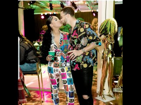 Ayesha Curry and her husband Steph share a kiss at her Jamaican themed surprise birthday party.