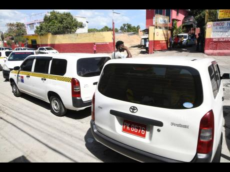 Taxi operators parked their vehicles to demonstrate the condition of a section of Waltham Park Road. But aided by the police, they attempted to rehabilitate the roadway and clear a nearby gully.