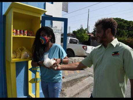 De'Andrea Jackson (left) and Kyle Reynolds (right) restock 'The Free Likkle Cupboard', at  Lady Musgrave Road in Kingston, which was established to help needy persons with food.