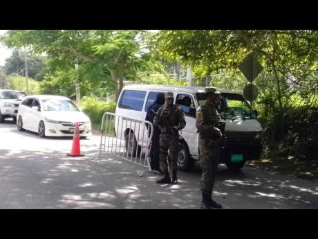 Members of the Jamaica Constabulary Force and the Jamaica Defence Force man a checkpoint.